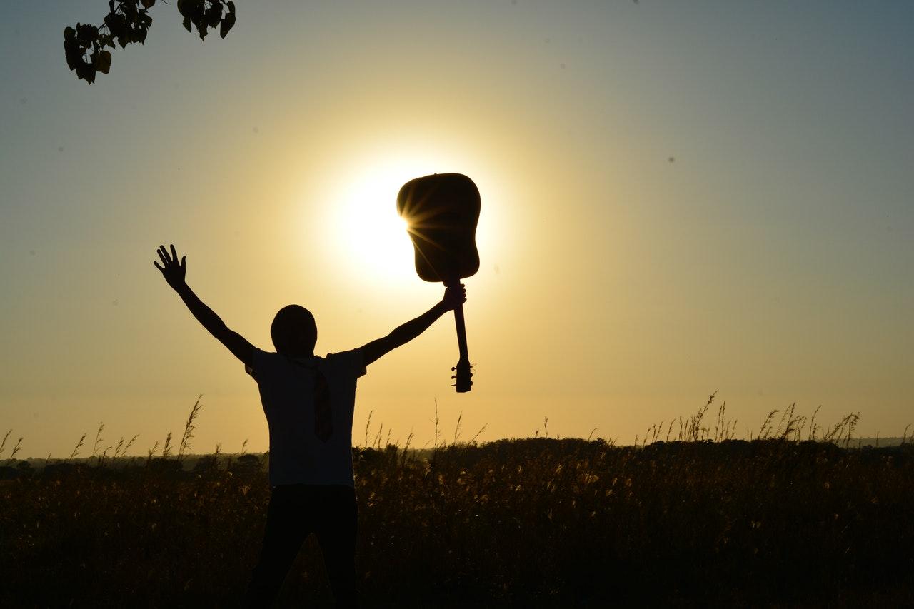Man raising his hands holding a guitar