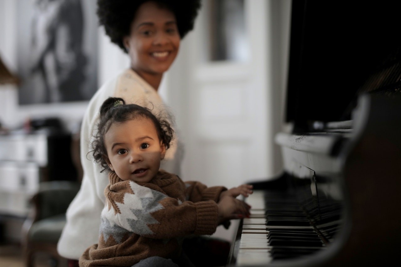 Toddler playing the piano with her mom