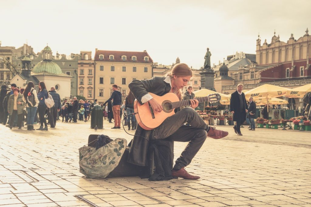 Man playing the guitar at a plaza